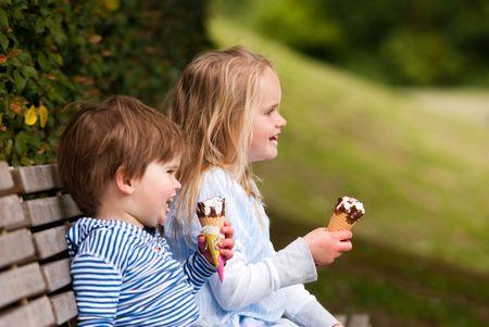 Ni�os sentados en Parque comer helado Foto de archivo - 5721155