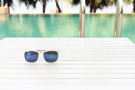 pool tables: sunglasses on wooden table by the pool Stock Photo
