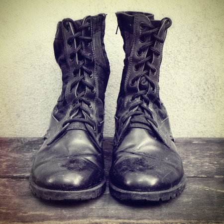 black boots: Old black boots on the wooden - vintage effect style