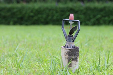 water sprinkler: Automatic water sprinkler on green grass.