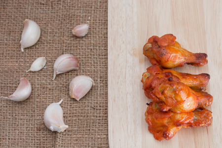 cutting boards: Chicken wings on wooden cutting boards with garlic on brow sack. Stock Photo