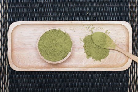 powdered: Powdered green tea on wooden tray placed on the mat. Stock Photo