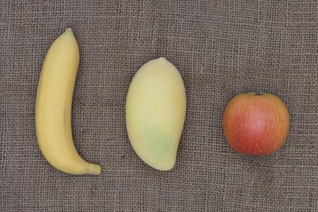 apple sack: Apple, banana and mango placed on the sack.