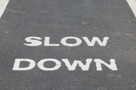 slow lane: A warnning sign SLOW DOWN painted on the bike lane Stock Photo