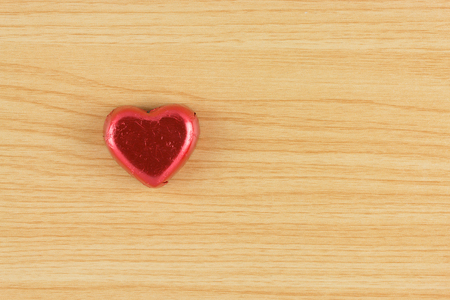 confections: chocolate candy red heart on wooden background. Stock Photo