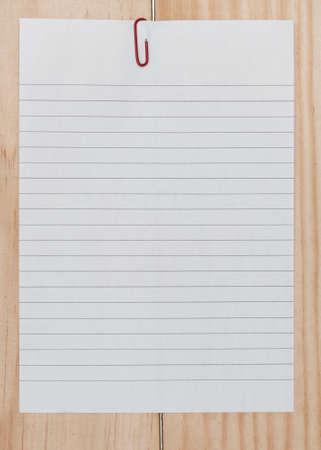 papier a lettre: Livre blanc avec trombone sur fond en bois. Banque d'images