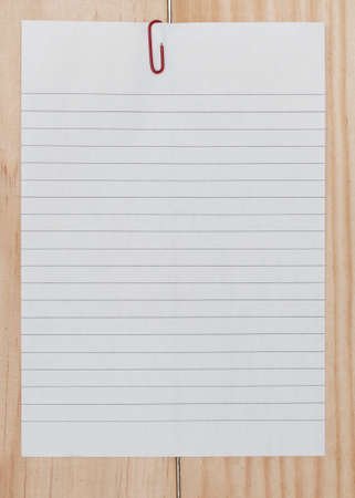 papier a lettre: white paper with paperclip on wooden background.
