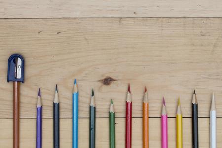sacapuntas: lápices de colores y sacapuntas en la mesa de madera.