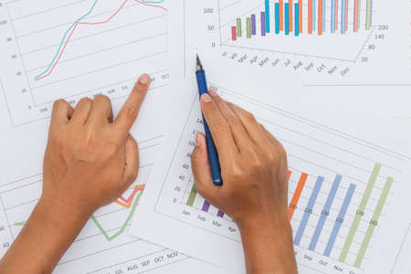 Businessman analyzing investment charts with stock market report as background
