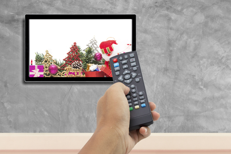 christmas decoration with hand holding remote control at television screen with concrete wall for background.