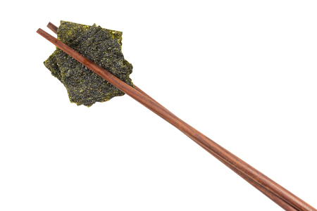 Sheet of dried crispy seaweed with chopsticks isolated on white background - clipping path