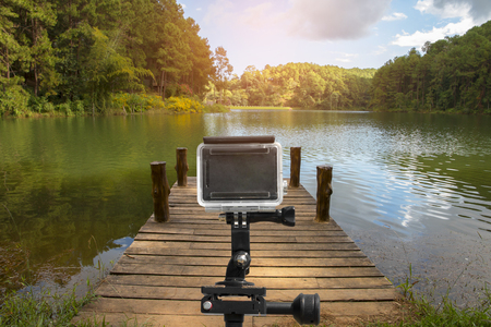 action camera on tripod with wooden dock beside lake.