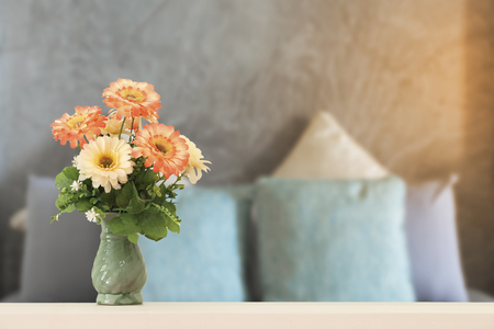 flowers in vase on wooden table with bedroom. Stock Photo