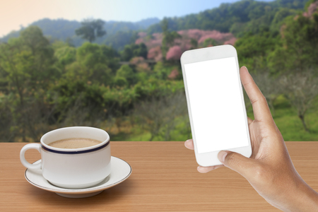 hand holding of smartphone and coffee on wooden table with nature background