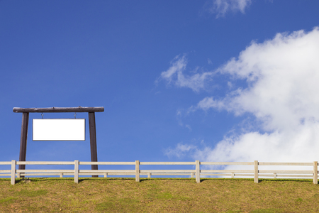 signboard and wood fence with grass and blue sky