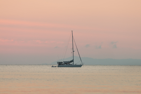 sailboat in the sea of summer background and sunset in the evening time. Stockfoto
