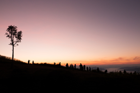 silhouette of people the cliff and looking at the valley and mountains with sunrise in the morning Stockfoto