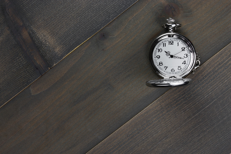 pocket watch on wooden table