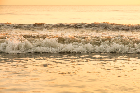 wave of sea on sandy beach in the evening time.