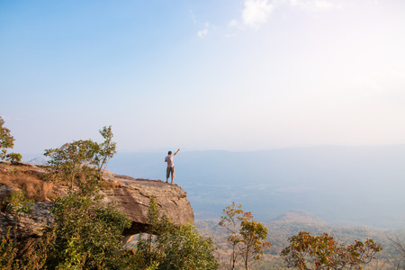 man standing on the cliff and looking at the valley and mountains