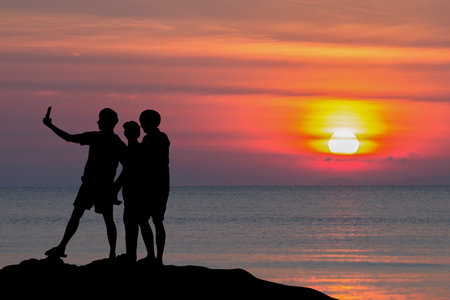 silhouette of people taking selfie at the beach with sunset in the evening.