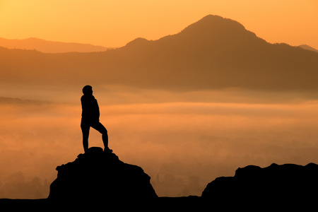 silhouette of a man standing on the mountains with sunrise in the morning.