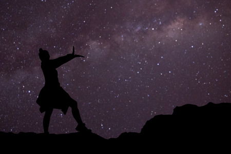 silhouette of a girl on the mountain with blurred of milky way background.