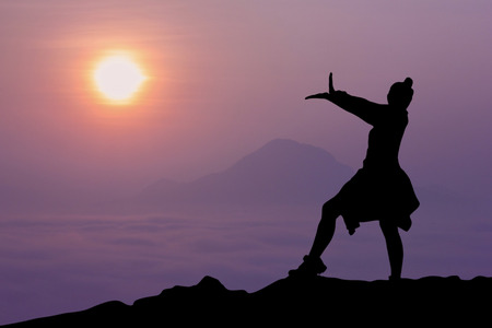 silhouette of a woman standing on the mountains with sunrise in the morning.