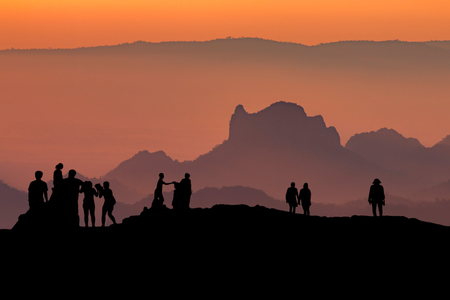 silhouette of people relax on the mountains with sunset in the evening. Stockfoto
