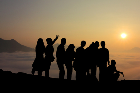 silhouette of people relax on the mountains with sunrise in the morning.