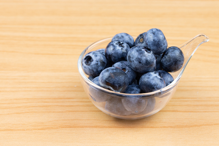 blueberry in cup on wood table background Stockfoto