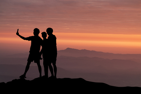 silhouette of people taking selfie at the cliff on mountains with sunset in the evening