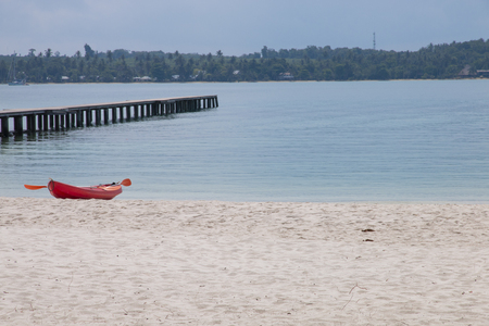 red kayak on the beach with tropical sea