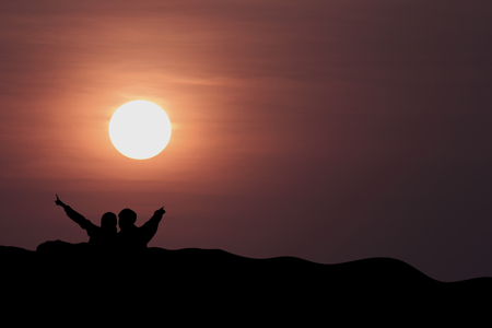 silhouette of man and woman on the mountain with sunset in the evening.