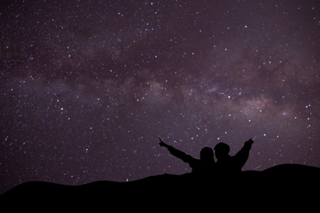 silhouette of man and woman on the mountain with blurred of milky way background. Stockfoto