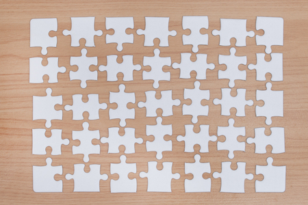 White jigsaw puzzle on wood background