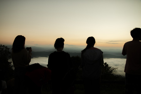 Silhouette of tourists in a high mountain valley with sunrise in the morning.