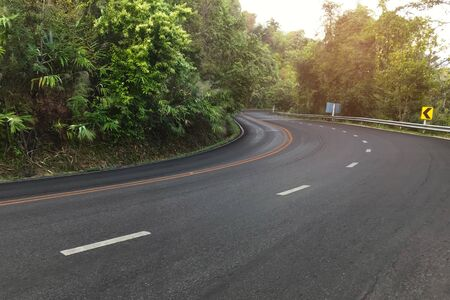 Asphalt road through in the forest.