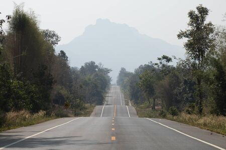 Driving on an empty asphalt road through with tree and mountain. Stockfoto