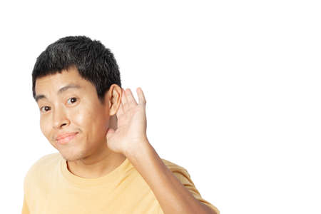 Young man with hand over ear listening and hearing to rumor or gossip. secret concept. isolated on white background. clipping path. Archivio Fotografico