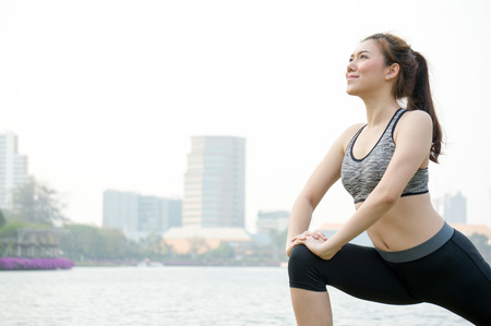 Asian woman people warm up for running and yoga  lunges in park for health with happiness fitness Stock Photo