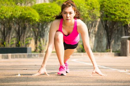 Aziatische sportvrouw klaar op beginpunt voor het lopen  jogging