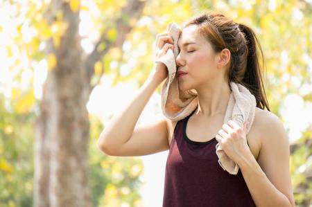 公園で運動のためのタオルを持つアジアのスポーツ女性