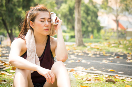 Asian sport woman is tried and rest after running in park