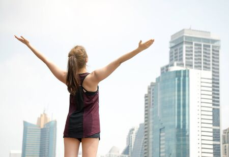 Asian sport woman feeling fresh and freedom in park located in center of city on building background Stock Photo - 87923057