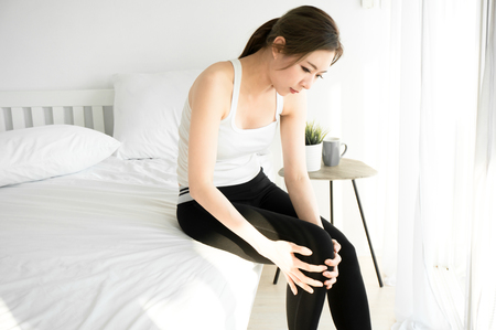 Asian woman have a knee ache on morning in bedroom Reklamní fotografie