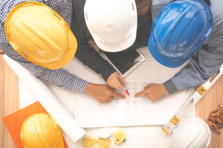De ingenieur en de voorman die veiligheidshelm dragen ontmoeten op plaats openlucht en richten op tekenings bovenaanzicht