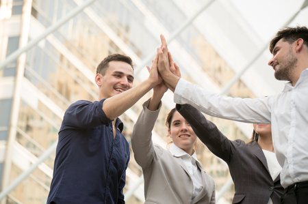 Businessman with colleagues hi five hand to cooperate on building background outdoor in city