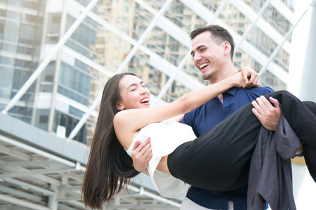 Couple man carry woman / girlfreind on building background outdoor in city