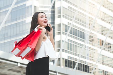 Asian woman holding shopping bag and calling on walking way in the city Standard-Bild